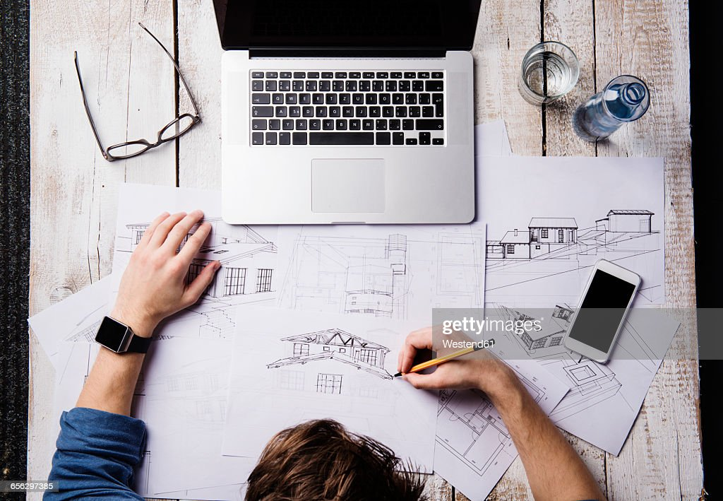 Architect working at desk with laptop, making sketches : Stock Photo