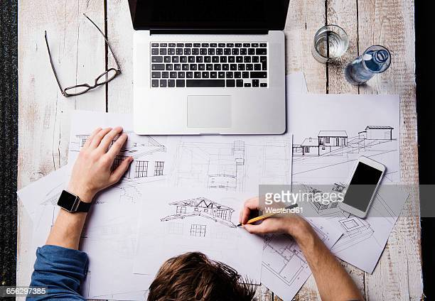Architect working at desk with laptop, making sketches