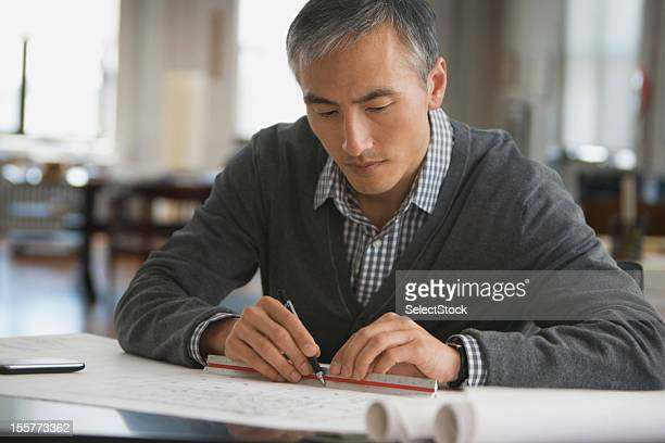 Architect working on blue prints