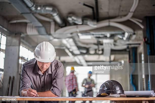 architect working on blueprint - mensen op de achtergrond stockfoto's en -beelden
