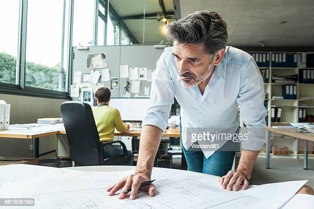 architect working on ground plan in office - architekturberuf stock-fotos und bilder