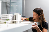 Architect Working Over Model In Office