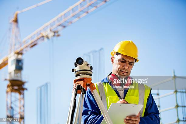 Architect writing on clipboard at site