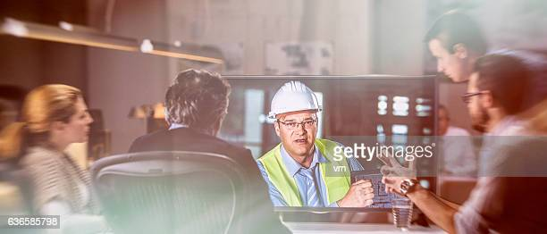 Architects and businessmen having video conference with engineer
