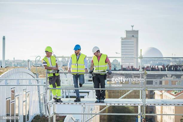 Architects and construction worker discussing on scaffolding at site