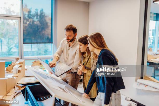 architects at university studying a blueprint - civil engineering stock pictures, royalty-free photos & images