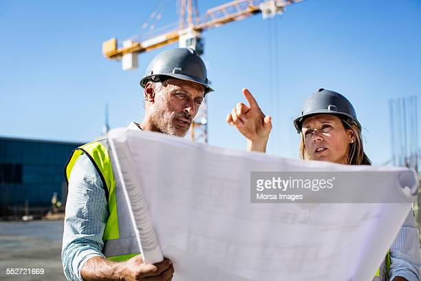 Architects discussing over blueprint at site