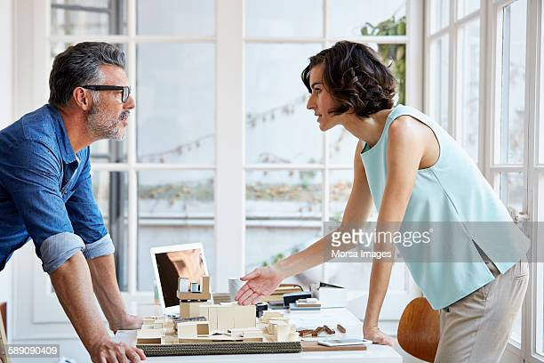 Architects discussing over building model