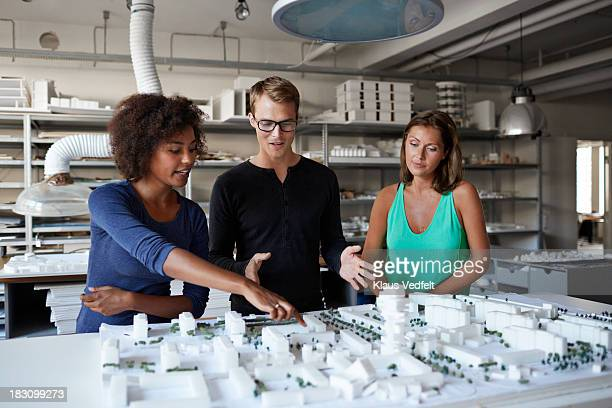 Architects discussing over model made of foam