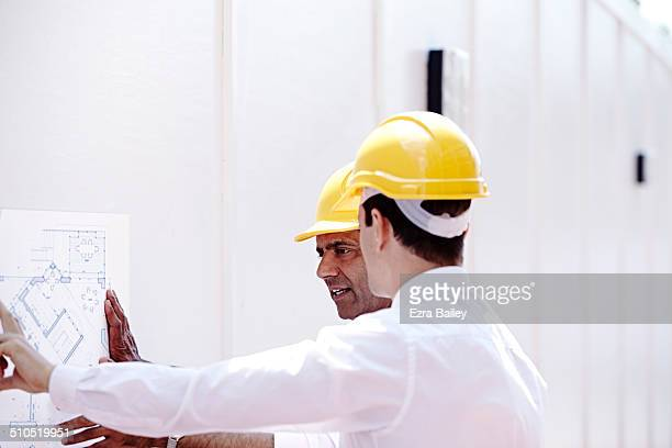 Architects discussing plans on a building site.