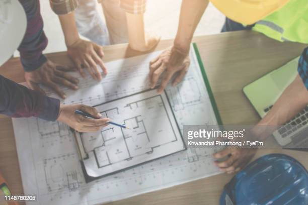 architects drawing blueprint at desk in office - blueprint stock pictures, royalty-free photos & images