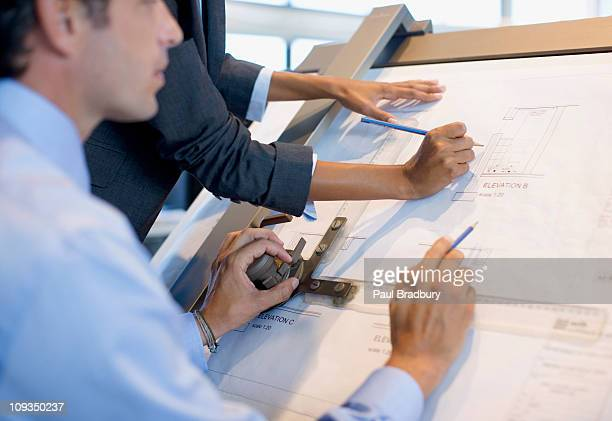 Architects drawing blueprints together in office