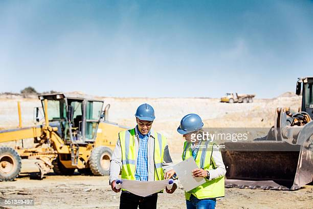 Architects examining blueprint at quarry