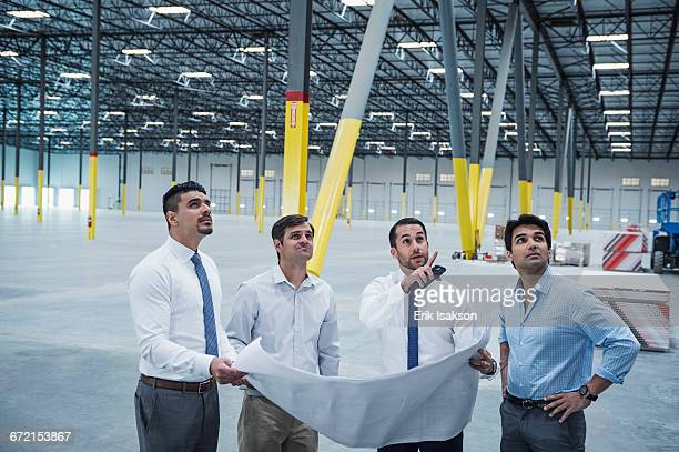 Architects examining blueprint in empty warehouse