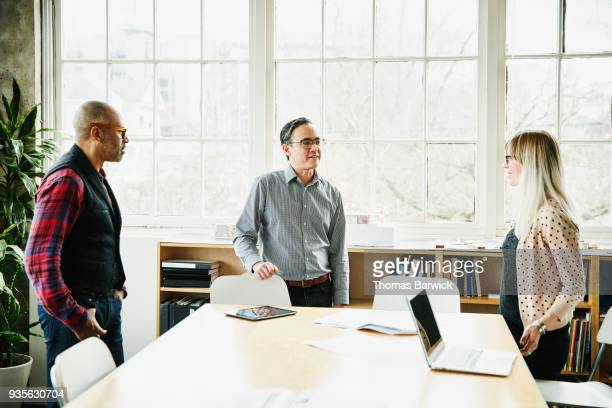 Architects having informal planning meeting at conference table in design office