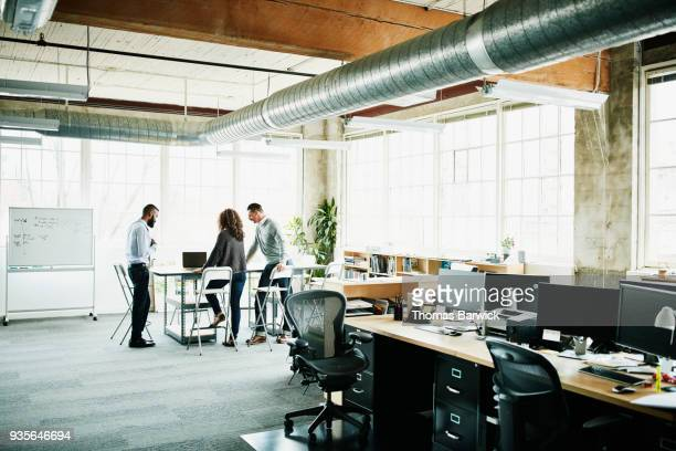 Architects having planning meeting at conference table in design studio