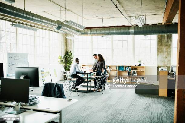 architects in project meeting at conference table in design studio - design studio stock pictures, royalty-free photos & images