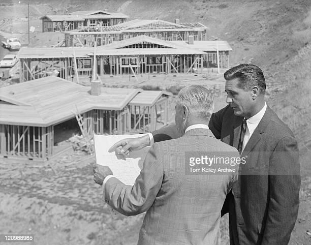 Architetti guardando cianografie vicino al Cantiere di costruzione