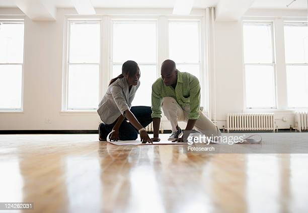 architects looking at blueprints in empty room - female bare bottoms stock pictures, royalty-free photos & images