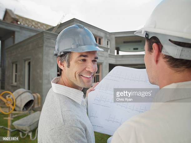 Architects looking at blueprints outside house under construction