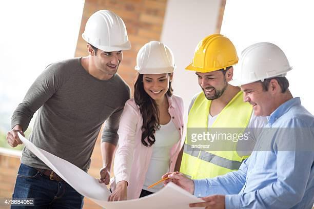 arquitectos mirando blueprints - ingeniero civil fotografías e imágenes de stock