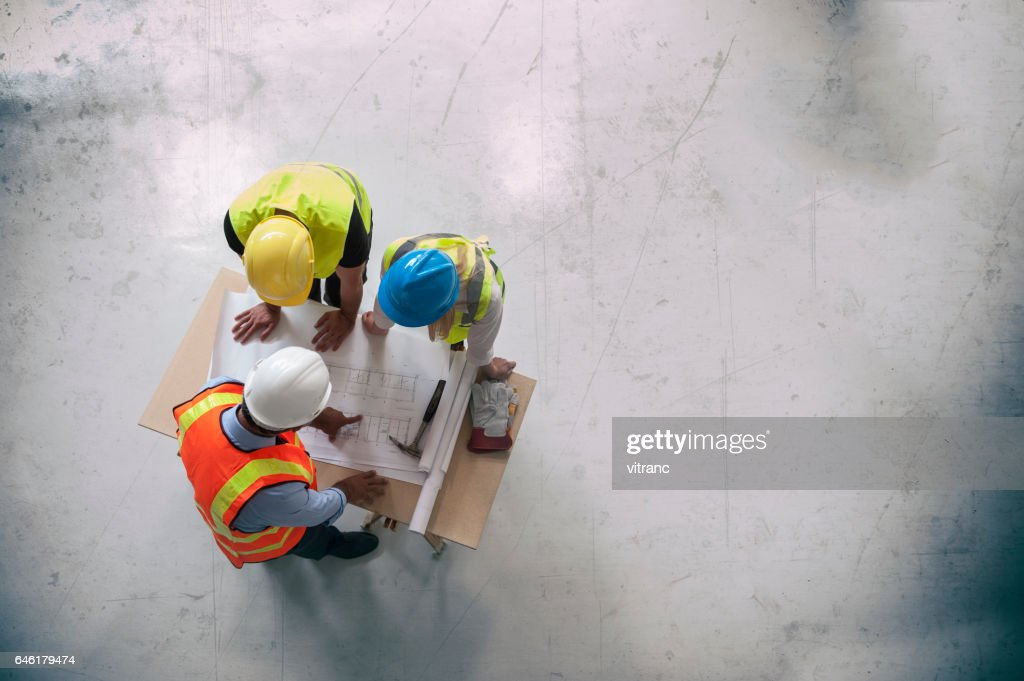Architects looking at blueprints : Stock Photo