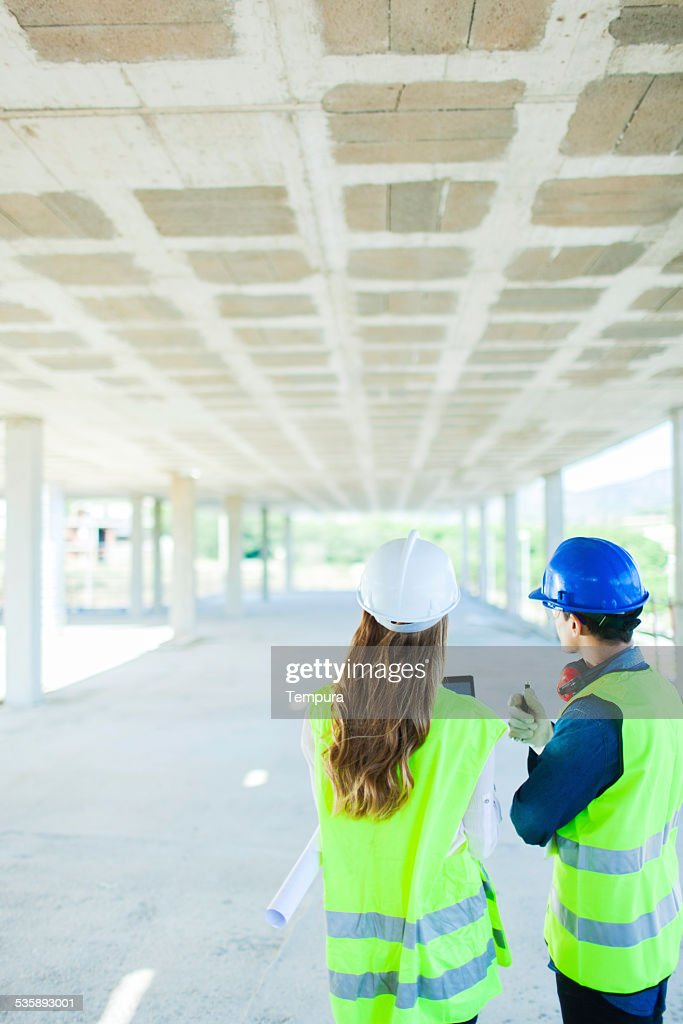 Architects looking at concrete structure. : Stock Photo
