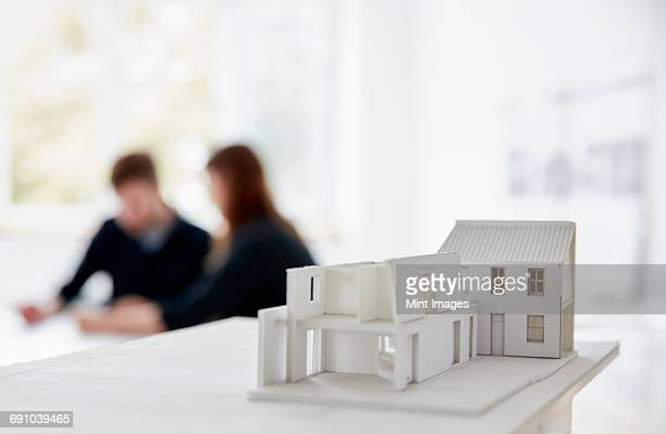Architects model of a building with two people at a meeting out of focus in the background. Communication.