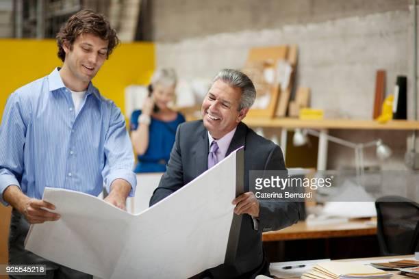 architects reading blueprints in office - zakelijke kleding stock pictures, royalty-free photos & images