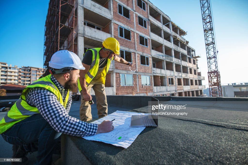 Architecten reviseren blauwdrukken op bouwplaats. : Stockfoto