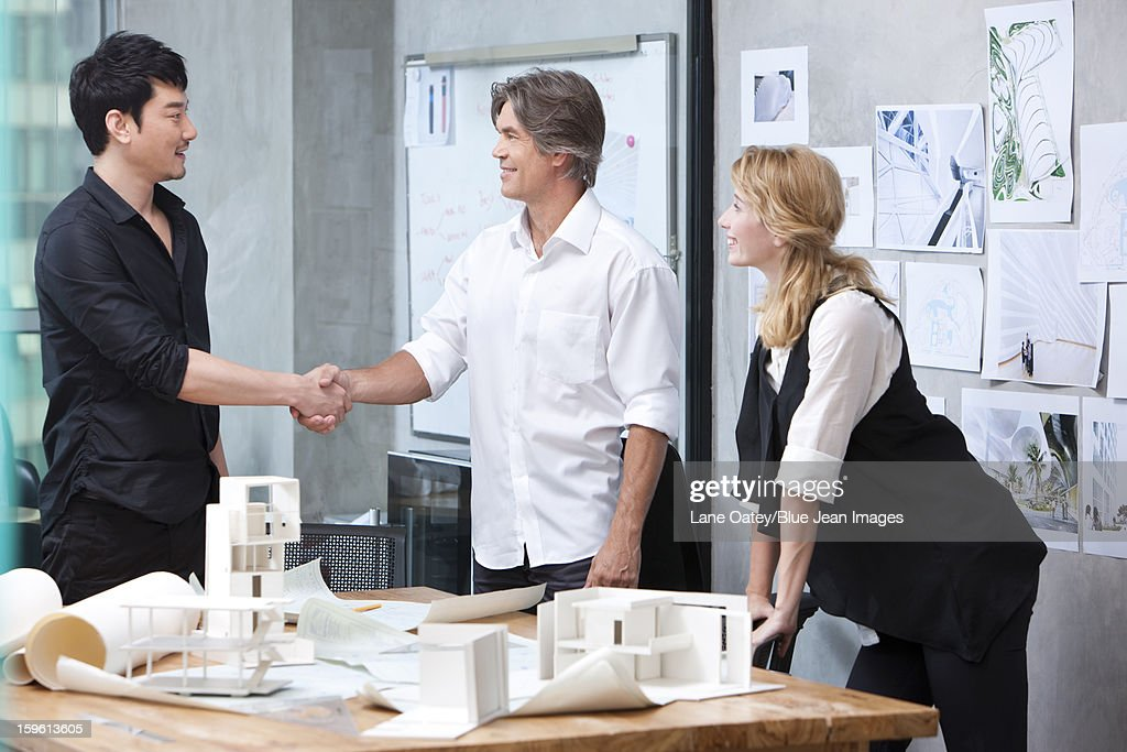 Architects shaking hands in studio : Stock Photo