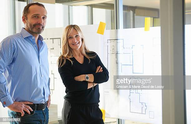architects standing by plans on glass wall - heterosexual couple stock pictures, royalty-free photos & images