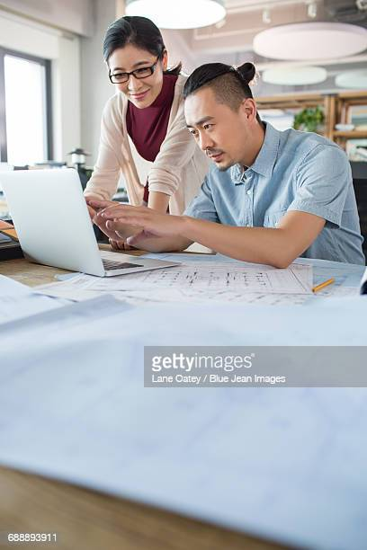 Architects talking with laptop in the office