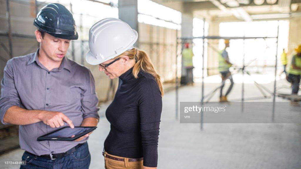 Architecten die een digitale tablet gebruiken en op een bouwplaats spreken : Stockfoto
