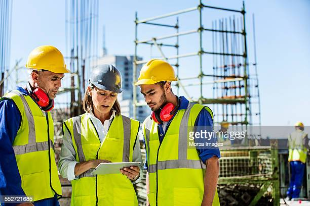 architects using digital tablet at site - construction industry stock pictures, royalty-free photos & images