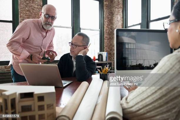 Architects using laptop in office