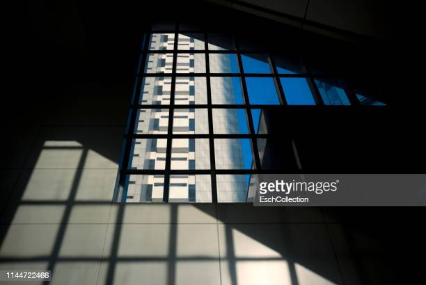 architectural abstract of large window, building, sky and shadow - ombra in primo piano foto e immagini stock