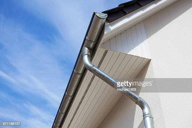architectural close-up of a metal rain gutter with downspout - eaves stock photos and pictures