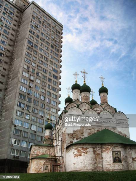 Architectural contrasts: towering socialist housing project against old Orthodox Church in Moscow, Russia