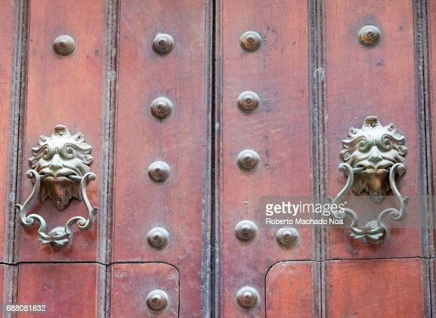 Architecture detail in Unesco World Heritage Site Closeup of an ornate wooden door adorned with metal buttons and lion door knockers