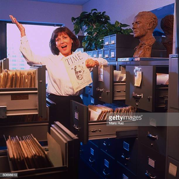 TIME archivist Elaine Felsher retiring after 27 yrs throwing up her arm amid her office files w 1922 TIME 1st preissue Jo Davidson bust of Henry Luce