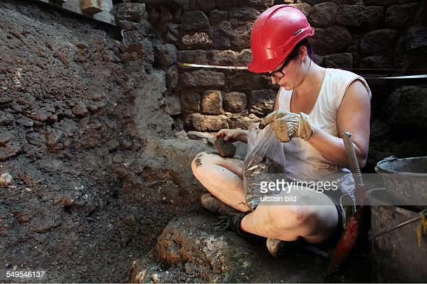 Archäologische Zone in Köln Archäologiestudentin gräbt an der Ostseite der Mikwe Die Erde wird in Eimern nach oben gezogen