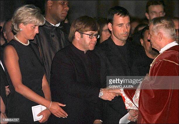 Archpriest Magio shakes hands with British rock star Elton John standing next to Princess Diana during the requiem mass for Italian fashion designer...