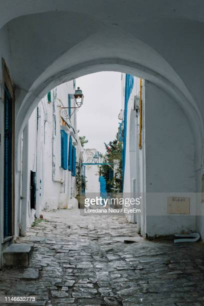 archway amidst buildings in city - tunis stock pictures, royalty-free photos & images