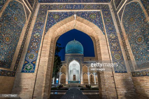 archway inlaid with vibrant mosaic tile patterns, the registan, a historic 15th century madrasa building. - oezbekistan stockfoto's en -beelden