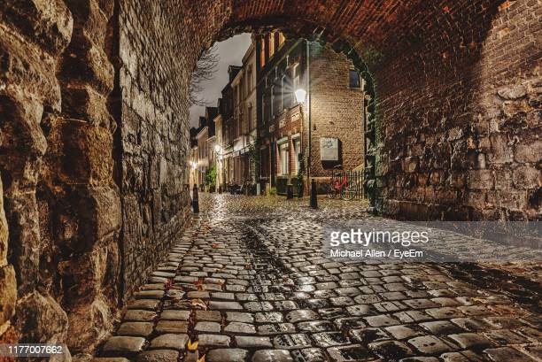 archway leading towards amidst buildings in illuminated city - マーストリヒト ストックフォトと画像