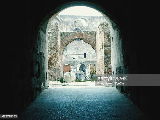 archway towards the old ruins of the coliseum - inside the roman colosseum stock photos and pictures