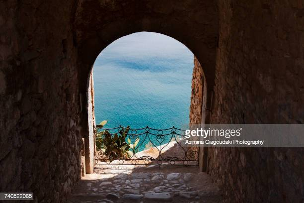 archway view of blue sea, nafplio, greece - peloponnese stock photos and pictures