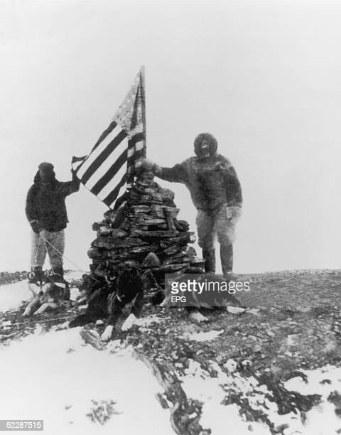 Arctic explorer and naval commander Robert Edwin Peary stands beside a cairn of stones supporting the American flag during his 1909 expedition to the...