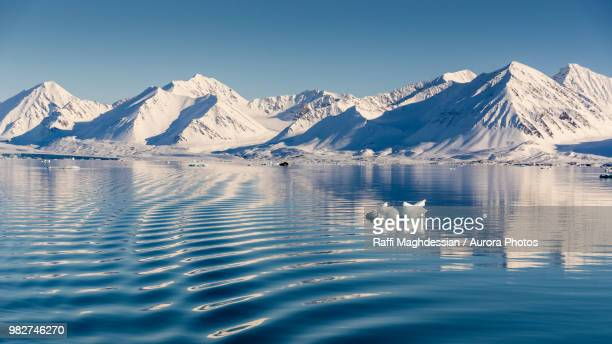 arctic scenery with snow covered mountains and sea, ny-alesund, spitsbergen, svalbard and jan mayen, norway - spitsbergen stock pictures, royalty-free photos & images